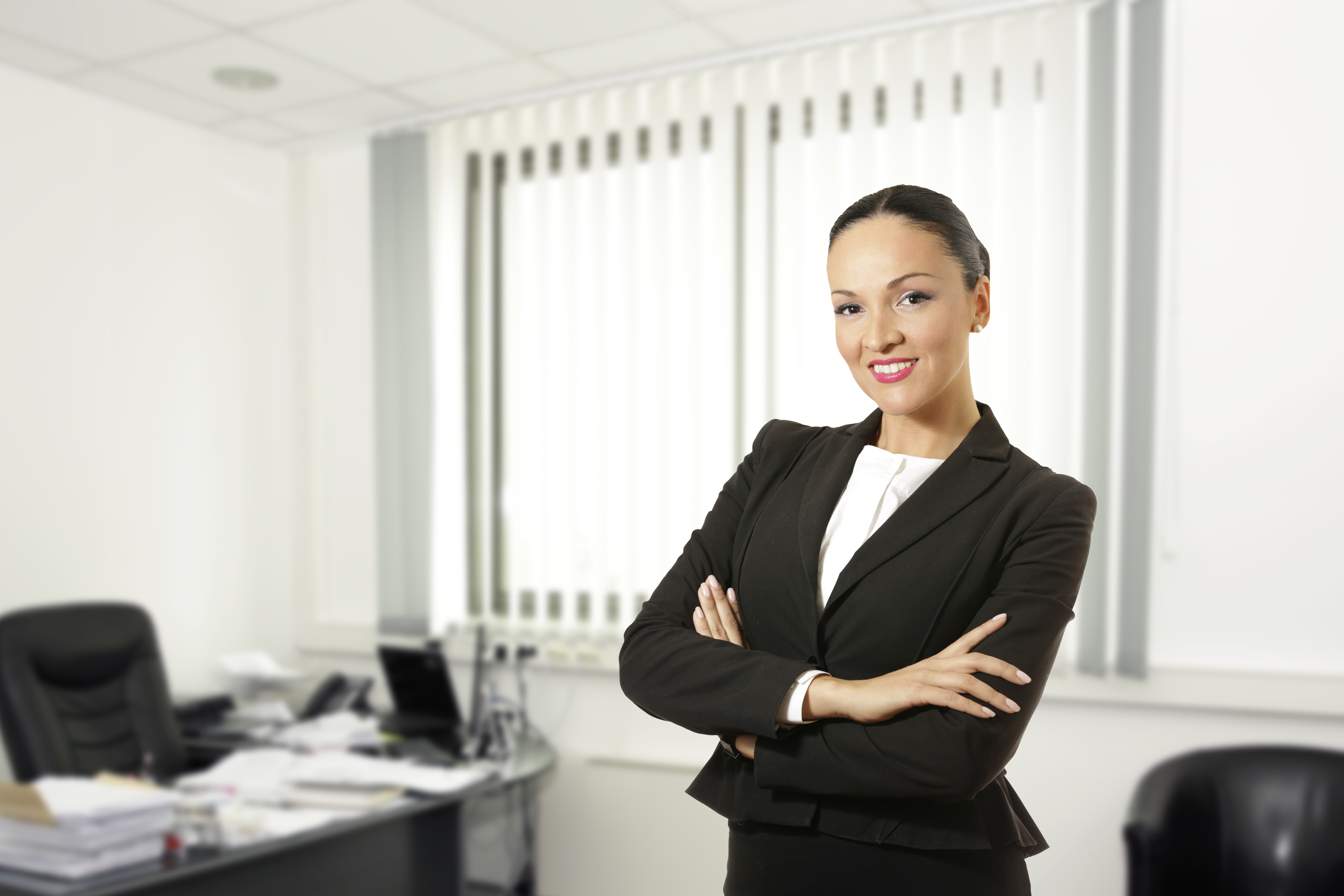 Successful young business woman inside her office.